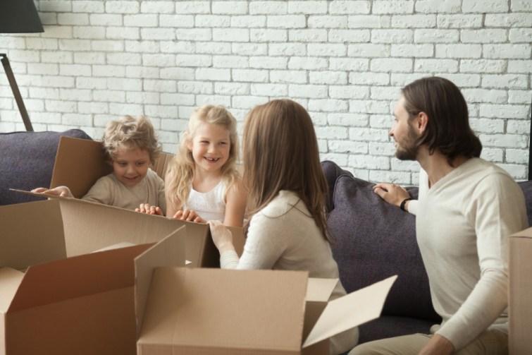 Kinder spielen mit Kartons beim Umzug