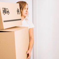 Frau mit Umzugskartons zieht wieder bei Eltern ein