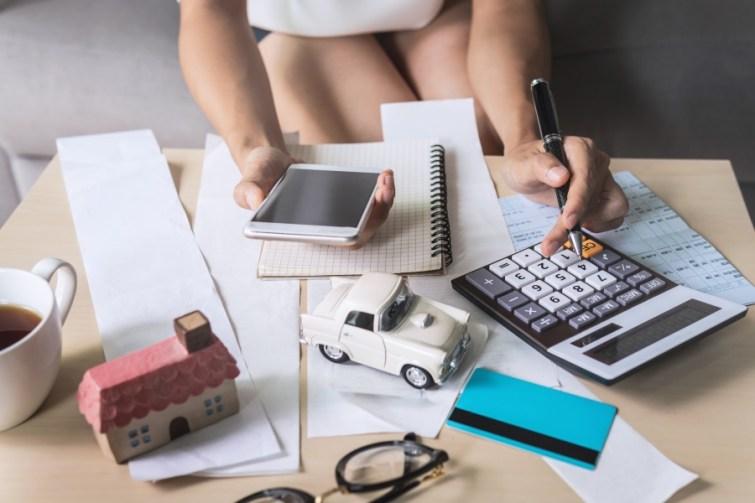 Frau berechnet Umzugsbudget um Geld zu sparen beim Umzug