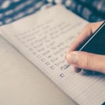 Hand schreibt Umzug Checkliste im Heft