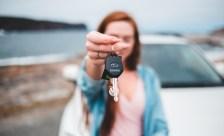 Frau zeigt Schlüssel von gemieteten Transporter