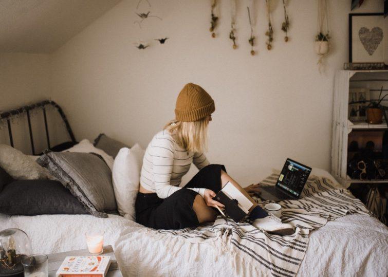 Junge Frau sitzt auf Bed in erster eigener Haushalt
