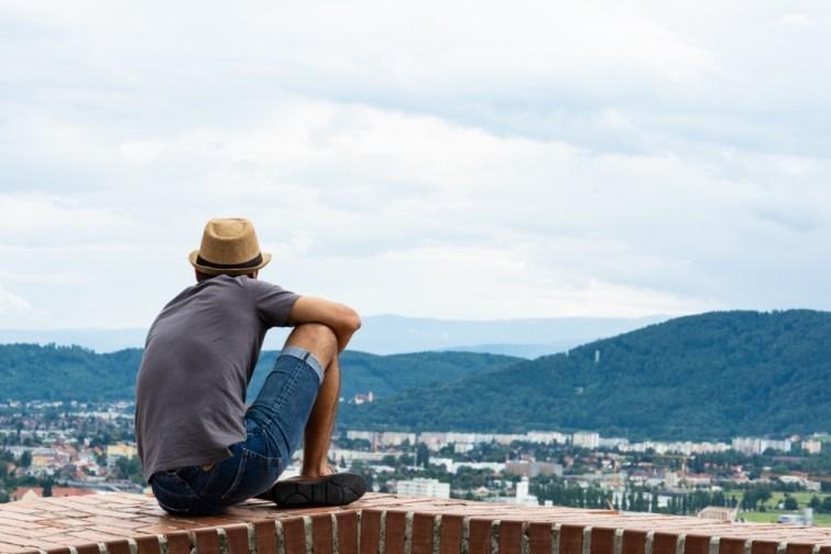 mann sitzt auf schlossberg und denkt über Umzug nach Graz