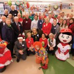 Rotary members pose with the Reds mascots before students arrive for the annual holiday party.