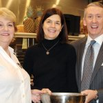 Betsy Eicher of the Urban Grill dishes up one of her specialties for auction chairs Kris and Steve Mullin.