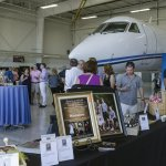 Guests view silent auction items at Concours Hangar Party.