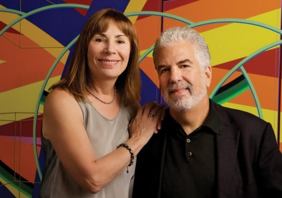 """Donna and Neal Mayerson. Photo by Tina Gutierrez. Painting: Al Held, """"B.C.,"""" 1979, acrylic on canvas, courtesy the Manuel D. and Rhoda Mayerson Foundation"""