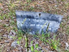 A piece of sheet metal with letters stamped into the sheet with the deceased;s name and dates.