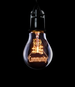 Hanging lightbulb with glowing Community concept.