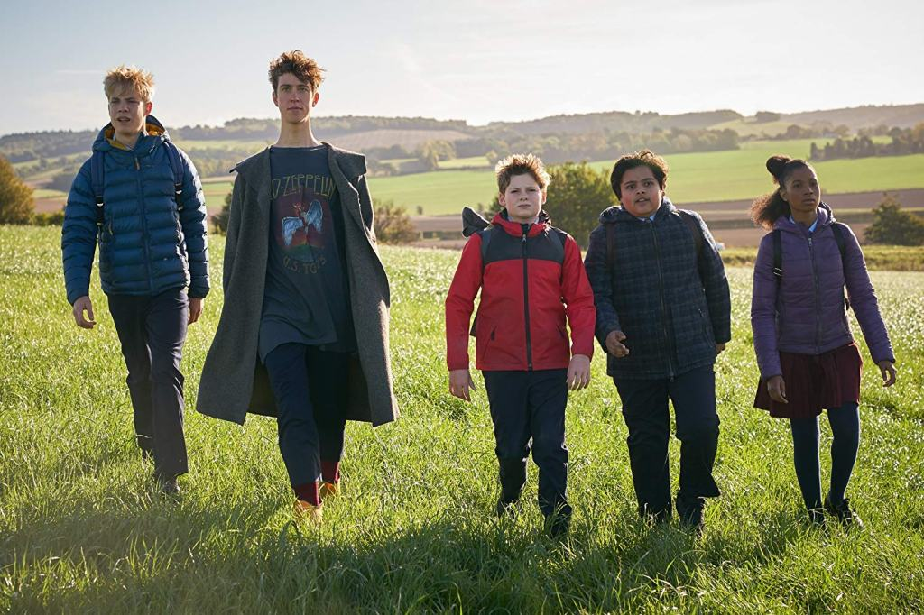 5 kids walking through a field
