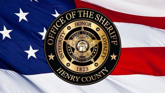 Photo of Henry County Sheriff's Office logo on American flag background