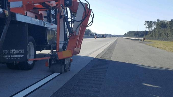 Photo shows a roadside vehicle applying new striping on I-75 (Georgia DOT photo)