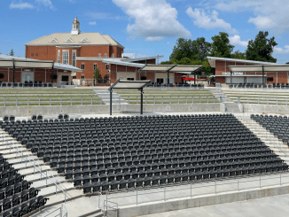 Photo of Stockbridge amphitheater with Stockbridge city hall in the background. Photo shows empty arena seating on a clear sunny day (staff photo).