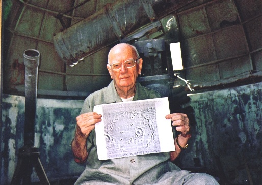 Sir Arthur Clarke, sitting next to the historic telescope, shows a photo of Crater Molesworth