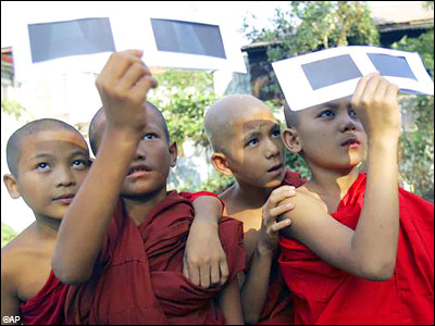 Myanmar Buddhist novices watch solar eclipse through the filters, in Yangon, Myanmar