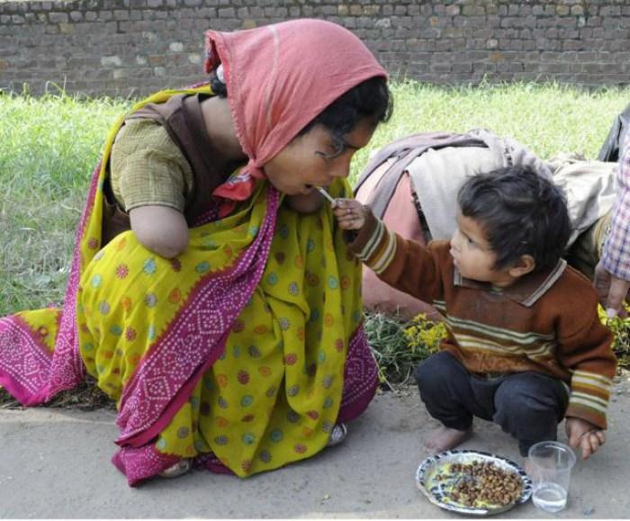 Un enfant de deux ans donne à manger à sa mère handicapée.