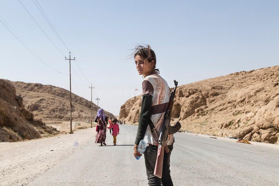 Une jeune fille yazidite porte un fusil d'assaut pour protéger sa famille contre Daech.