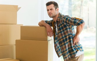 man leaning on boxes with strain in back