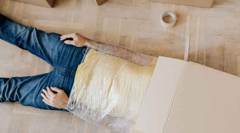 man with head in box and wrapped body on floor