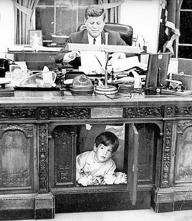 President Kennedy, working late at his White House office, wears a slight smile on his face, indicating perhaps he is not completely unaware that his son, John Jr., is exploring under his desk in the Oval Office in the White House in 1963. (AP, Look Magazine)