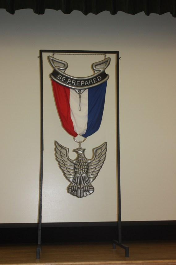 A large Eagle badge is a stage prop often available for loan from your local council.