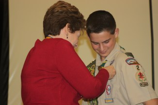 Moms usually get to pin the new badge on their son's well-used uniform.