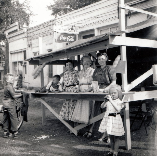 Here's the Graham Street Fair, circa 1958. I don't know the kid on the bicycle. I'm the one relaxing on the counter of the booth. Don't you love my cowboy shirt with the pearl buttons? When I went to the Street Fair, I was styling. The lady to my left is my Grandmother, Juanita Boring Mowry.