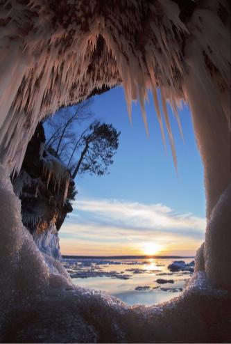 "Photo: Michael DeWitt. He said: ""In late December, a friend and I launched a canoe from the pack ice at Meyer's Beach, gateway to the mainland sea caves in the Apostle Islands National Lakeshore. We broke skim ice and dodged ice bergs out to the caves, and we were well rewarded for our efforts. I made the image from the canoe, through a port hole as the sun set across Mawikwe Bay."" Tweeted by the US Department of the Interior, 5/2/14."