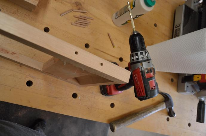 The side pieces were drilled for the dowels on the drill press; it's now time to extend those holes into the end pieces.