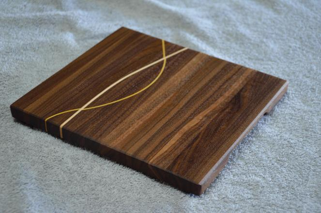# 12 Cheese Board, $35. Black Walnut edge grain with Yellowheart and Hard Maple inlays.