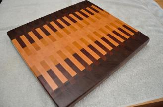 "# 66 Cutting Board, $150. Black Walnut, Jatoba, Padauk, Yellowheart and Hard Maple. 18"" x 16"" x 1-1/2"". End grain."