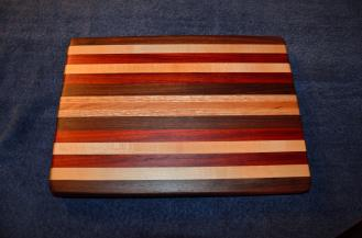 "# 22 Cutting Board, $60. Edge grain. Walnut, maple, padauk, oak, and cherry. 16"" x 12"" x 1-1/4""."