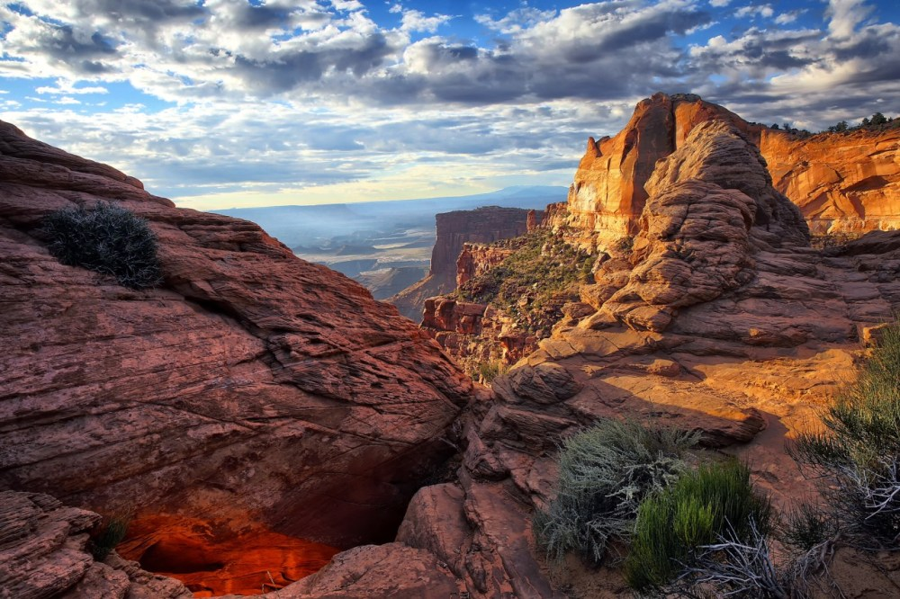 """Canyonlands National Park preserves 337,598 acres of colorful canyons, mesas, buttes, fins, arches and spires in the heart of southeast Utah's high desert. William Rainey captured this amazing photo of early morning light illuminating part of the park's iconic Mesa Arch and the surrounding rock formations. Of the experience, William says, """"Sometimes the best photo is not the one you came for."""" Photo courtesy of William Rainey. Posted on Tumblr by the US Department of the Interior, 12/11/14."""