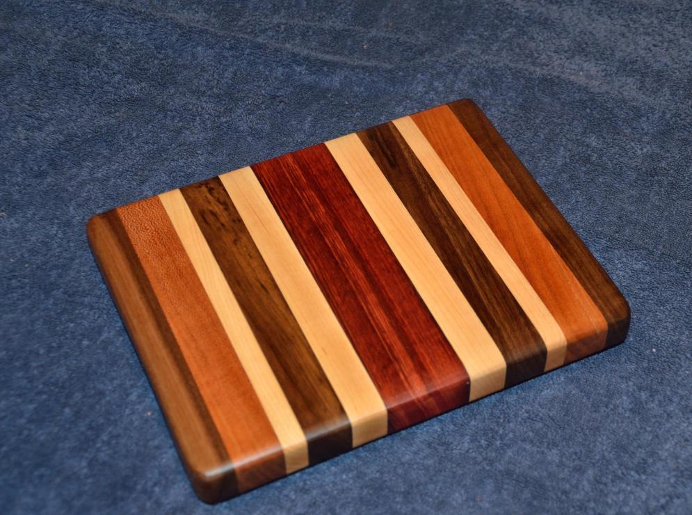 "Cheese board. Black Walnut, Cherry, Hard Maple and Jarrah. 8"" x 11"" x 1""."