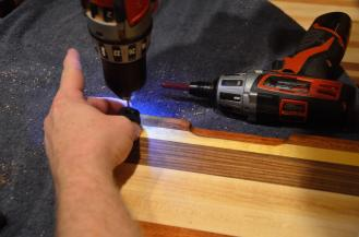 Feet are added to most boards after the wax is cleaned up. Holes have to be pre-drilled for the screws - the wood is too hard to simply drill in with a self-tapping screw. Further, many of the woods will crack if the holes are not pre-drilled.