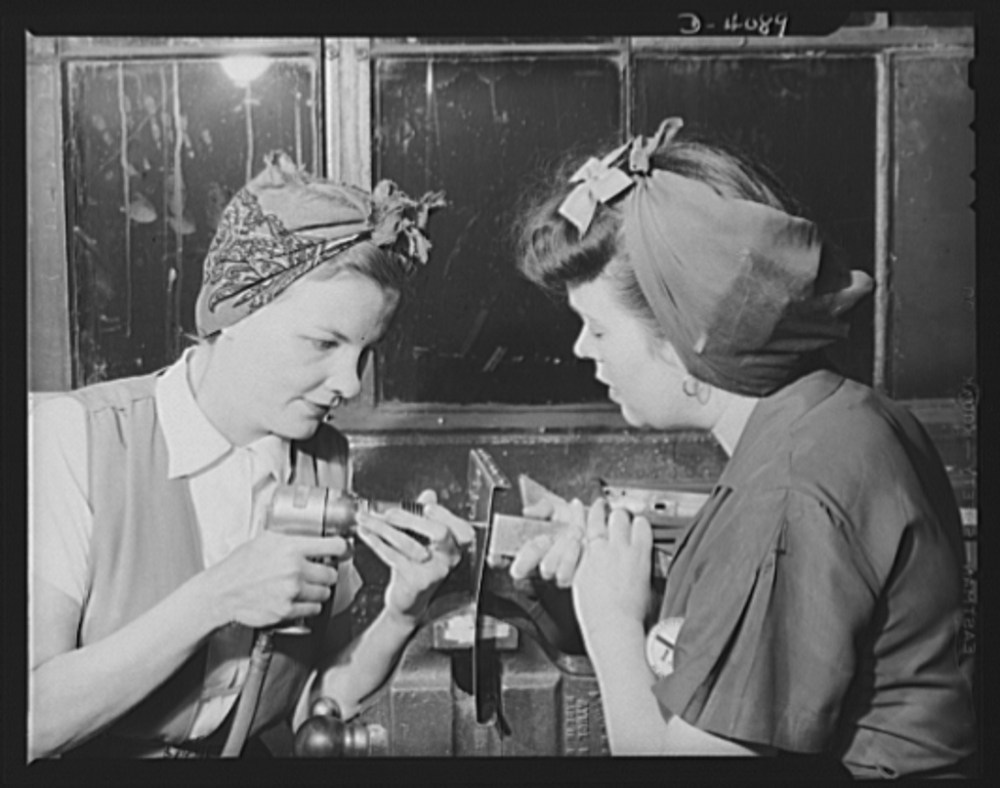 Women aircraft workers. Two Pearl Harbor widows work to defeat the Axis at a West Coast aircraft plant. Mrs. Fern Evans, left and Mrs. Evelyn J. W. Casola work as a team on the riveting of radio support assemblies for bomber planes. Neither had previous mechanical experience prior to this job, but both are now successfully handling complicated mechanical jobs. From the Office of War Information archive, May 1942.