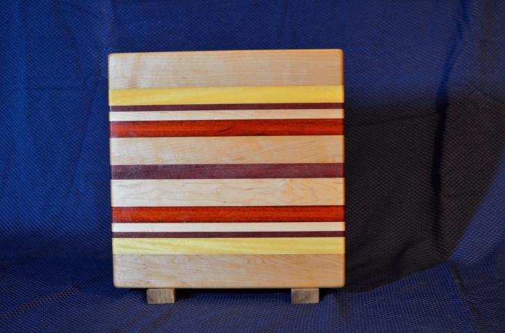 "Cutting Board # 15 - 081. Hard Maple, Yellowheart, Purpleheart & Padauk. 12"" x 12"" x 1-1/4""."