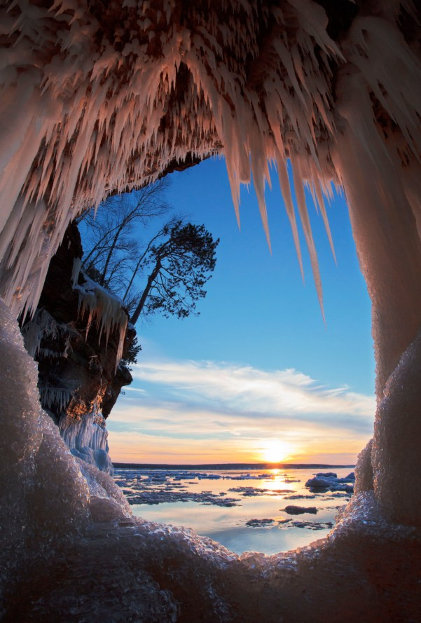 """Over thousands of years, Lake Superior carved out caves in the sandstone cliffs of the Wisconsin lakeshore. Today, when conditions are right, you can hike out across the solid water (ice) and see these remarkable formations clad in snow and ice at Apostle Islands National Lakeshore. Photo of """"The Keyhole"""" by Michael DeWitt. Posted on Tumblr by the US Department of the Interior, 12/29/15."""