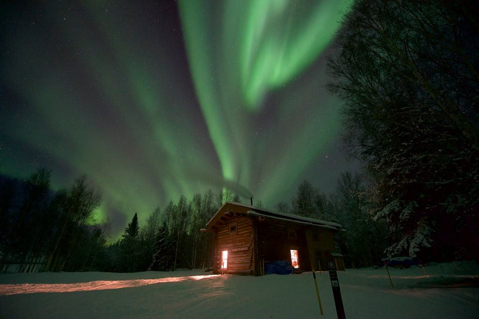 The Northern Lights shimmer above the remote Slaven's Roadhouse at Yukon-Charley Rivers National Preserve in Alaska. This historic roadhouse along the Yukon River once housed prospectors during the Klondike Gold Rush. Today, park visitors can spend the night in this restored cabin. Photo by Sean Tevebaugh, National Park Service. Posted on Tumblr by the US Department of the Interior, 3/31/16.
