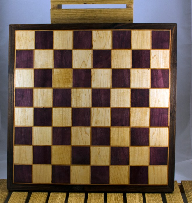 "Chess 16 - 06. Playing surface is Purpleheart & Hard Maple, with the squares framed in Cherry. Board is framed in Black Walnut. Squares are 2-1/8"" across."