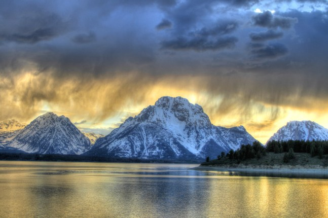Wispy clouds float over Jackson Lake as the sun slowly sinks behind the Teton mountains at Grand Teton National Park in Wyoming. Photo by Shelley Davault. Posted on Tumblr by the US Department of the Interior, 5/14/16.