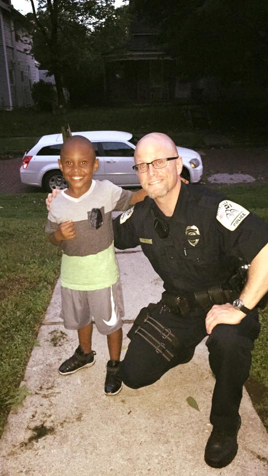 """Paul Anderson, being a good cop on July 13, had these words, """"I made a new friend today! He said he wants me to be a police officer when he grows up, so of course he got an Honorary Police Badge! He was so happy! """"We may not mean something to everyone in the whole world, but some days we can mean the whole world to one person."""""""