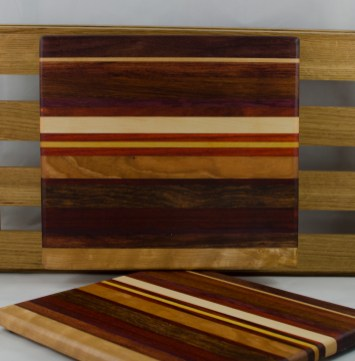 "Cheese Board 16 - 037. Chaos Board. Black Walnut, Cherry, Bubinga, Bloodwood, Padauk, Hard Maple & Yellowheart. 9"" x 11"" x 3/4""."