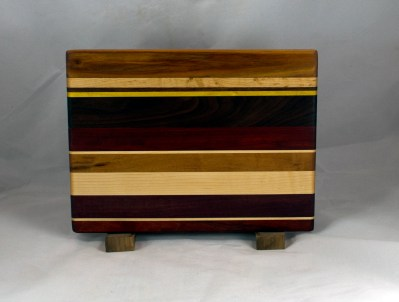 "Cheese Board 16 - 056. Chaos Board. Canarywood, Padauk, Hard Maple, Yellowheart, Black Walnut, Goncalo Alves & Bloodwood. 9"" x 12"" x 5/8""."