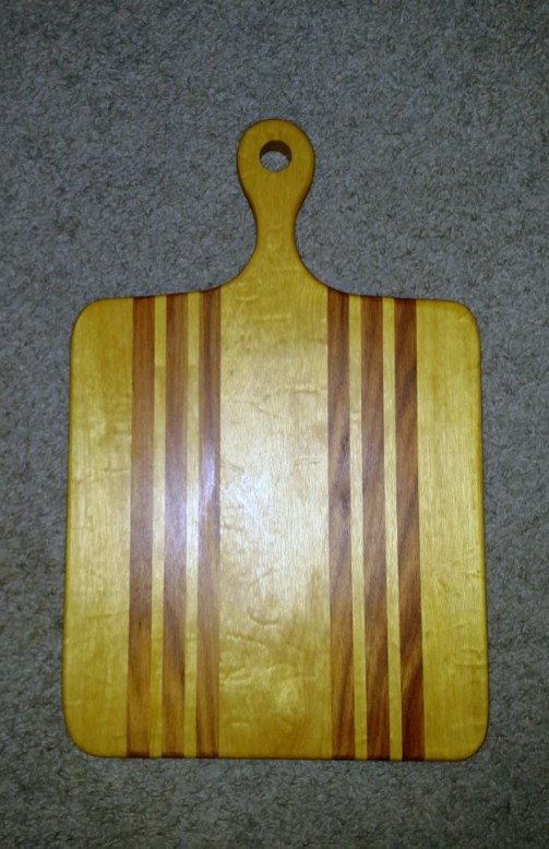 "Small Sous Chef 16 - 024. Quilted Yellowheart & Canarywood. 9"" x 16"" x 3/4""."