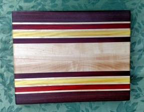 "Engraved 17 - 025. Edge grain cutting board with the back engraved. Purpleheart, Hard Maple, Padauk, Yellowheart & Bubinga. 14"" x 18"" x 1-1/4"". Purchased before it was completed."