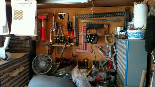 The garage's original workbench, installed by our home's original buyer, is overwhelmed by the things I try to keep close at hand.