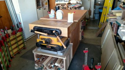 The workbench is the center of any shop. Here, I've got a glue-up waiting to happen on top ... while the planer & a stack of cut-offs are stored underneath. Space cannot be wasted. Ever.