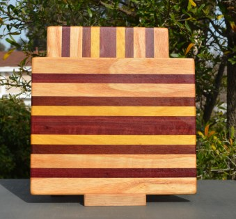 "Cheese Board 18 - 101. Honey Locust, Purpleheart, Bloodwood & Yellowheart. 9"" x 11"" x 5/8""."