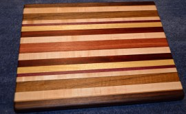 """Cutting Board # 15 - 027. Commissioned piece. This is the """"World Traveler"""" board with woods from 5 continents. Black Walnut, Hard Maple and Cherry, from North America. Yellowheart and Jatoba from South America. Teak from Asia. Padauk and Purpleheart from Africa. Jarrah from Australia. Edge grain. 13"""" x 16"""" x 1-1/4""""."""
